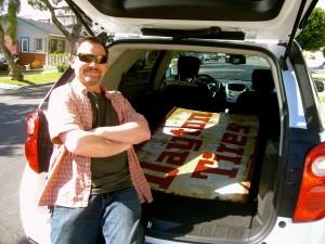 Clark with his Dayton Tires sign, which barely fit in the rental car.